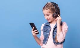 Chica joven que escucha la música con los auriculares Fotografía de archivo