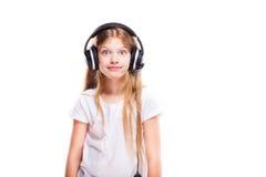 Chica joven que escucha la música con los auriculares sobre blanco Imagenes de archivo