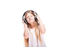 Chica joven que escucha la música con los auriculares sobre blanco Fotos de archivo libres de regalías