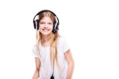 Chica joven que escucha la música con los auriculares sobre blanco Fotos de archivo