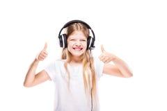 Chica joven que escucha la música con los auriculares sobre blanco Imagen de archivo libre de regalías