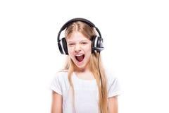 Chica joven que escucha la música con los auriculares sobre blanco Foto de archivo