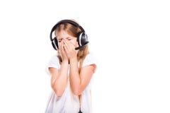 Chica joven que escucha la música con los auriculares sobre blanco Imágenes de archivo libres de regalías