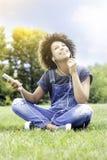 Chica joven que escucha la música en el parque, relajándose Imágenes de archivo libres de regalías