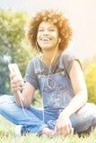 Chica joven que escucha la música en el parque, relajándose Imagen de archivo
