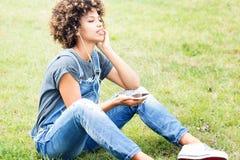 Chica joven que escucha la música en el parque, relajándose Foto de archivo