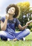 Chica joven que escucha la música en el parque, relajándose Imagenes de archivo