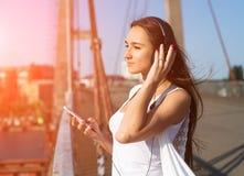 Chica joven que escucha la música en parque Estudiante afuera con los auriculares Imagen de archivo