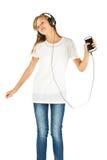 Chica joven que escucha la música en su smartphone sobre la parte posterior del blanco Foto de archivo libre de regalías