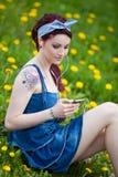 Chica joven que escucha la música en un parque Fotos de archivo libres de regalías