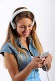 Chica joven que escucha la música en un reproductor Mp3 Fotografía de archivo libre de regalías