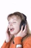 Chica joven que escucha la música y que canta Fotos de archivo libres de regalías
