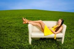 Chica joven que escucha la música y que descansa sobre el sofá   Imágenes de archivo libres de regalías