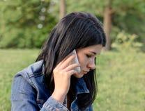 Chica joven que escucha una llamada en su móvil Imagen de archivo libre de regalías