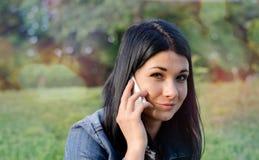 Chica joven que escucha una llamada en su móvil Imagen de archivo