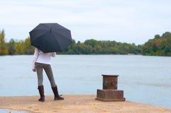 Chica joven que espera en el muelle del río Fotografía de archivo