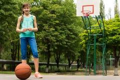 Chica joven que espera para jugar a baloncesto Imagenes de archivo
