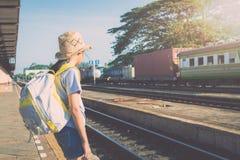 Chica joven que espera un tren en el ferrocarril Imagenes de archivo