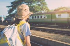 Chica joven que espera un tren en el ferrocarril Foto de archivo