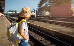 Chica joven que espera un tren en el ferrocarril Fotos de archivo