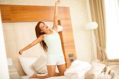 Chica joven que estira después de sueño imagenes de archivo