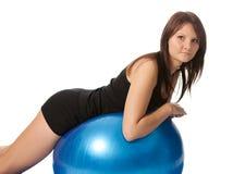 Chica joven que estira detrás en bola de la aptitud Imágenes de archivo libres de regalías