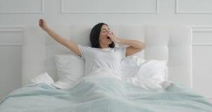Chica joven que estira el cuerpo en cama metrajes