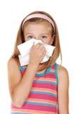 Chica joven que estornuda. Fotografía de archivo