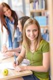 Chica joven que estudia en la biblioteca de la High School secundaria Imágenes de archivo libres de regalías