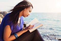 Chica joven que estudia su biblia por el mar Fotos de archivo libres de regalías
