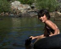 Chica joven que flota en el tubo Imágenes de archivo libres de regalías