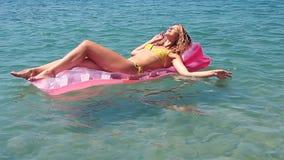 Chica joven que flota en un colchón en el mar almacen de video