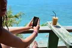 Chica joven que fotografía el café de hielo Foto de archivo