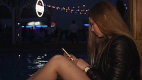 Chica joven que golpea ligeramente en smartphone en la piscina en club nocturno Partido holidays almacen de metraje de vídeo
