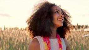 Chica joven que goza de la lluvia del confeti en el campo de trigo durante puesta del sol metrajes