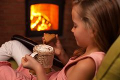 Chica joven que goza de una galleta con un chocolate caliente que se sienta por fotografía de archivo