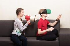 Chica joven que grita a través del megáfono en el muchacho que lleva los vidrios de la realidad virtual 3D, sentándose en el sofá Fotos de archivo libres de regalías