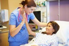 Chica joven que habla con la enfermera de sexo femenino In Hospital Room Fotos de archivo libres de regalías