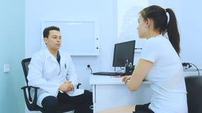 Chica joven que habla de sus problemas con la mano al doctor almacen de video