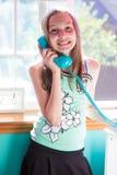 Chica joven que habla en el teléfono en su sitio Imagenes de archivo