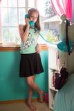 Chica joven que habla en el teléfono en su sitio Imagen de archivo
