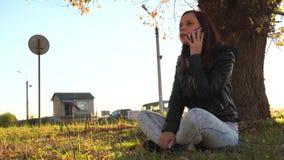 Chica joven que habla en el teléfono en el otoño en el parque en la puesta del sol