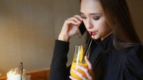 Chica joven que habla en el teléfono, sonriendo y bebiendo el zumo de naranja recientemente exprimido en café indoor almacen de metraje de vídeo