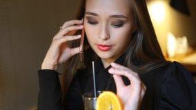 Chica joven que habla en el teléfono, sonriendo y bebiendo el zumo de naranja recientemente exprimido en café indoor almacen de video