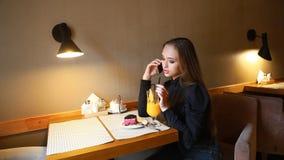 Chica joven que habla en el teléfono, sonriendo y bebiendo el zumo de naranja recientemente exprimido y comiendo el pastel de que almacen de metraje de vídeo