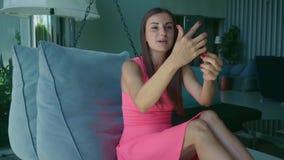 Chica joven que habla en Skype en el teléfono mientras que miente en una cama colgante por la tarde, cámara lenta almacen de video