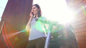 Chica joven que habla en un smartphone y que lleva a cabo una mano en la vespa eléctrica, resplandor del sol almacen de metraje de vídeo