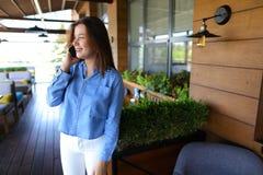 Chica joven que habla por smartphone en el restaurante Fotografía de archivo