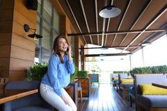 Chica joven que habla por smartphone en el restaurante Foto de archivo