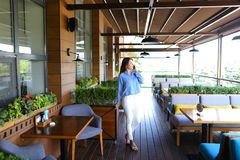 Chica joven que habla por smartphone en el restaurante Foto de archivo libre de regalías